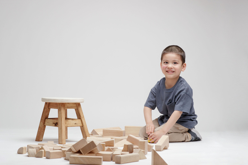 Energetic, excited boy plays with blocks during family session